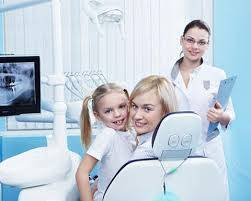 Mother daughter on a dental chair with assistant